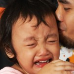 A crying little girl with tears in her eyes