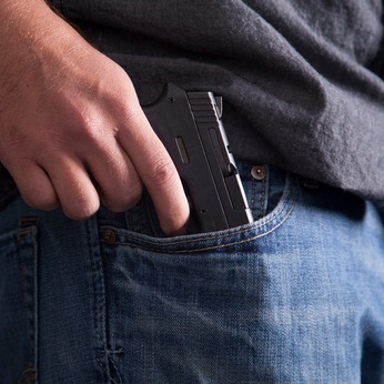 A man pulls a concealed firearm out of his pocket.