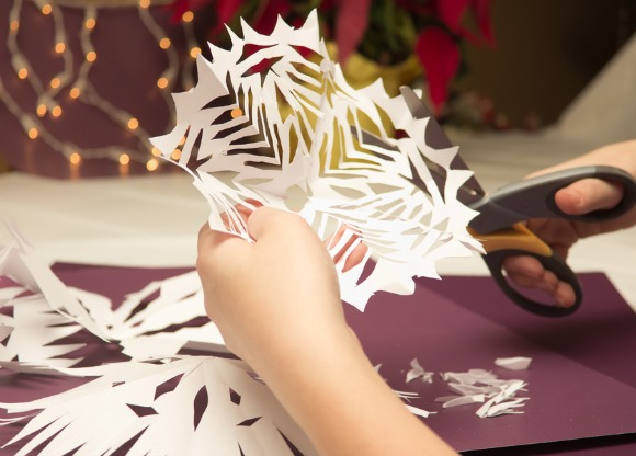 Paper snowflakes are one of many fun, easy DIY holiday decorations you can do as a family.