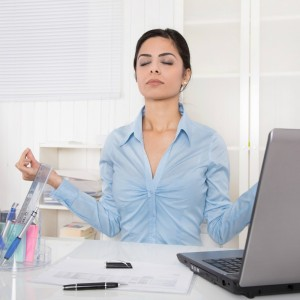 Pretty manager with closed eyes is doing meditation at office.