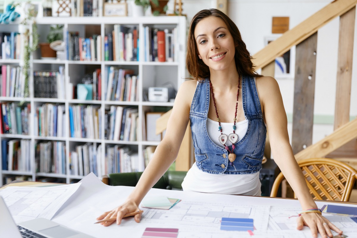 Smiling young designer standing in creative office in front of her desk