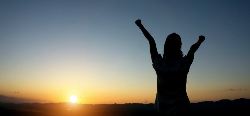 silhouette woman Hands up against sunset time with lens flare
