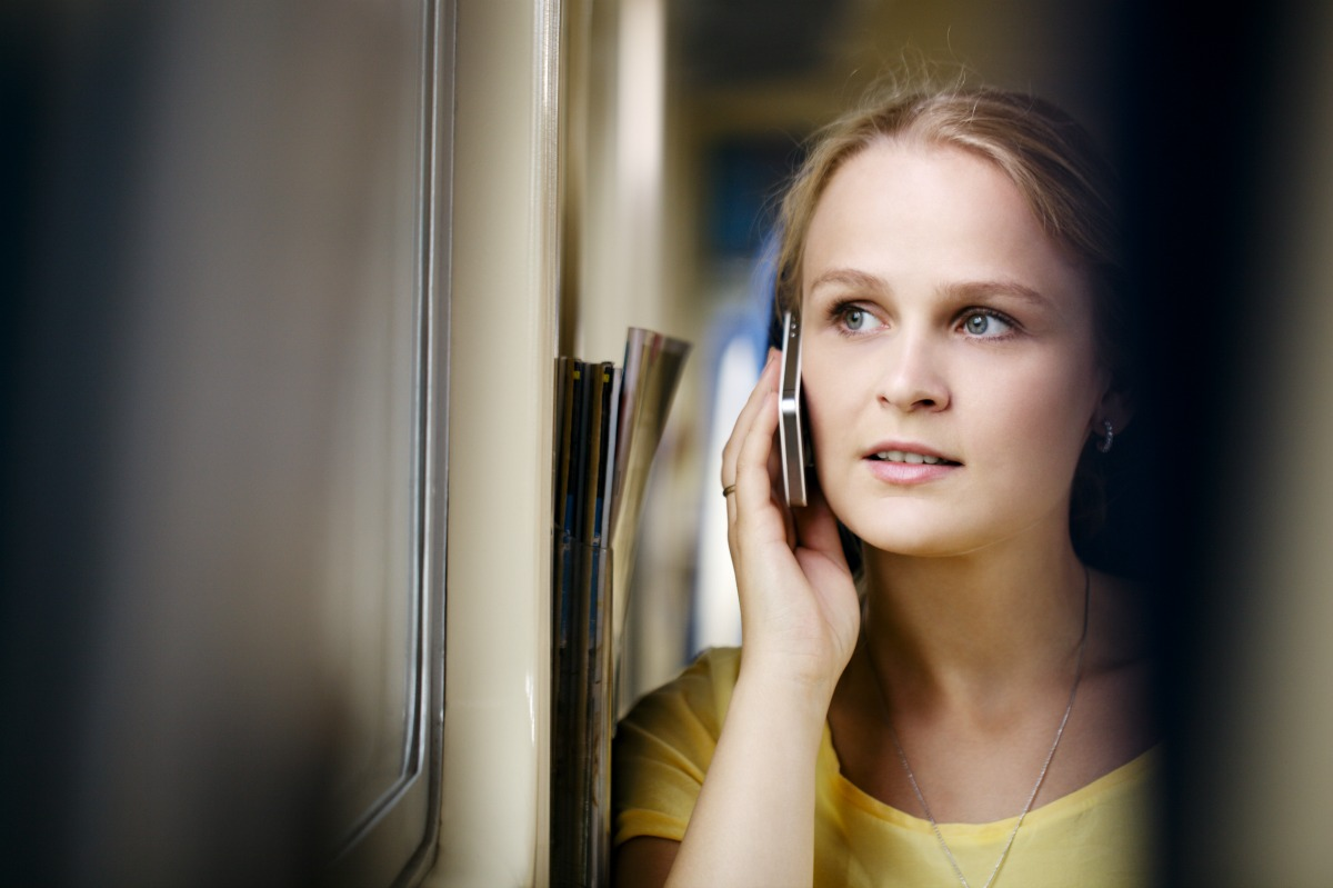 Young woman talking on the phone in the train and looking out the window.